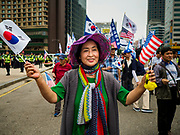 09 JUNE 2018 - SEOUL, SOUTH KOREA: A woman with South Korean and American flags marches in a pro-American rally in downtown Seoul. Participants said they wanted to thank the US for supporting South Korea and they hope the US will continue to support South Korea. Many were also opposed to ongoing negotiations with North Korea because they don't think Kim Jong-un can be trusted to denuclearize or to not attack South Korea.     PHOTO BY JACK KURTZ