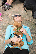 Woman with her chihuahua on her chest resting on a mountaintop