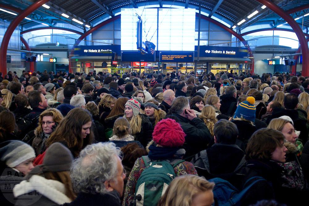 Reizigers wachten in de stationshal van Utrecht CS. Door sneeuwval is het treinverkeer ernstig ontregeld. Op Utrecht Centraal zijn veel reizigers gestrand. Slechts mondjesmaat rijdt een trein.<br /> <br /> Travelers are waiting at Utrecht CS. Due to the snow the Dutch railways are facing big problems. Lots of travelers are stuck on Utrecht Central Station. Only a few trains will depart.