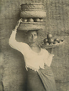 Woman in cloth and jacket carrying baskets with fruit.<br /> Photograph by Skeen.