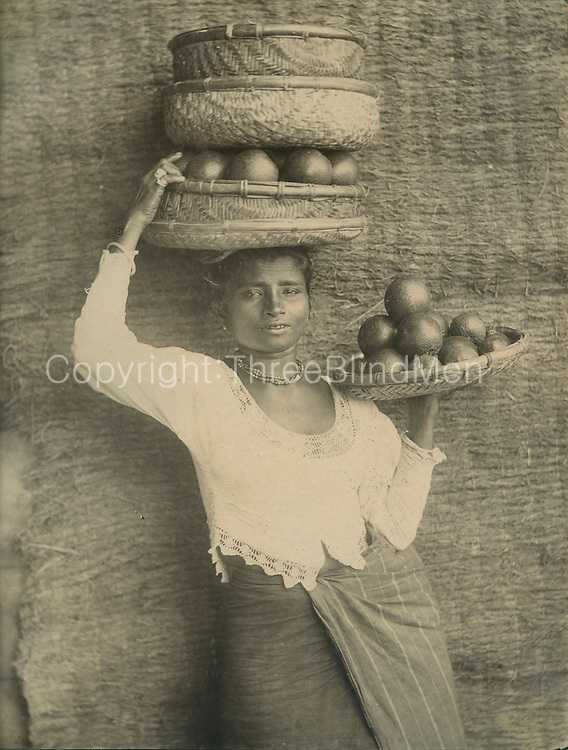Woman in cloth and jacket carrying baskets with fruit.<br />
