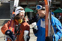 Two skiers laugh as they walk through Whistler Village on a sunny winter day while carrying a coffee.