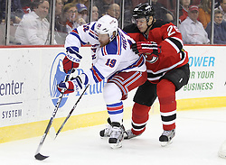 Mar 6; Newark, NJ, USA; New York Rangers center Brad Richards (19) skates with the puck while being defended by New Jersey Devils defenseman Anton Volchenkov (28) during the first period at the Prudential Center.