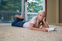 Portrait of girl (7-9) lying on carpet with book hand on chin