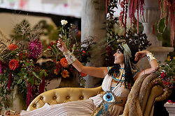 © Licensed to London News Pictures. 13/09/2018. HARROGATE, UK. An actress posing as Queen Cleopatra poses on a bed of rose petals, the Queen is said to have used rose petals as an elixir of love. Harrogate Autumn Flower Show runs from 14-15 September with over 5,000 blooms and an expected attendace of 60,000 visitors at the Yorkshire Showground in Harrogate..  Photo credit: Nigel Roddis/LNP