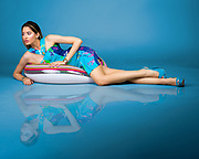 Fashion model Elodie Tusac poses on pool inner tube in simulated studio water shot.