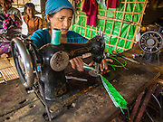 07 NOVEMBER 2014 - SITTWE, RAKHINE, MYANMAR: A Rohingya Muslim woman uses her foot powered sewing machine in an IDP camp for Rohingya. She was a seamstress before she was forcibly relocated to the camp and was allowed to bring her sewing machine. Many Rohingya were forced into the camps at gunpoint and not allowed to bring any personal belongings. After sectarian violence devastated Rohingya communities and left hundreds of Rohingya dead in 2012, the government of Myanmar forced more than 140,000 Rohingya Muslims who used to live in and around Sittwe, Myanmar, into squalid Internal Displaced Persons camps. The government says the Rohingya are not Burmese citizens, that they are illegal immigrants from Bangladesh. The Bangladesh government says the Rohingya are Burmese and the Rohingya insist that they have lived in Burma for generations. The camps are about 20 minutes from Sittwe but the Rohingya who live in the camps are not allowed to leave without government permission. They are not allowed to work outside the camps, they are not allowed to go to Sittwe to use the hospital, go to school or do business. The camps have no electricity. Water is delivered through community wells. There are small schools funded by NOGs in the camps and a few private clinics but medical care is costly and not reliable.   PHOTO BY JACK KURTZ