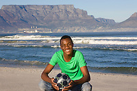 Young man with football on Table Mountain beach