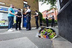 © Licensed to London News Pictures. 22/07/2016. LONDON, UK.  Police officers speak to a local resident next to a bunch of flowers that have been left on the street outside West Ham Lane Recreational Ground, known as Stratford Park on West Ham Lane in Stratford, where a man in his 20's was stabbed and killed yesterday afternoon. Two men were arrested nearby on suspicion of murder and taken into custody at an east London police station. Photo credit: Vickie Flores/LNP