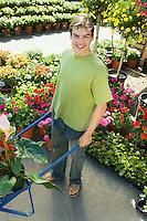 Young Man Pushing Wheelbarrow at Nursery