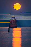 A full, super moon rises behind the Sandy Point Lighthouse, on the Chesapeake Bay, Near Annapolis, Maryland.