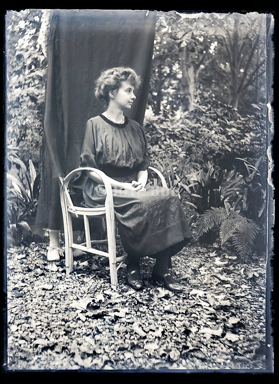 woman sitting for portrait in garden setting France ca 1920s