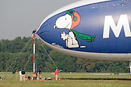 Montgomery, NY- The ground crew, including one man on the mooring mast,  prepare the Met Life blimp Snoopy Two for take off from Orange County Airport on July 26, 2008.