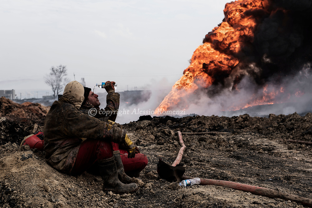 Iraq, Qayyara: Iraqi firefighters take a break as they try to extinguish oil wells put on fire by ISIS members as they were retreating. Alessio Romenzi