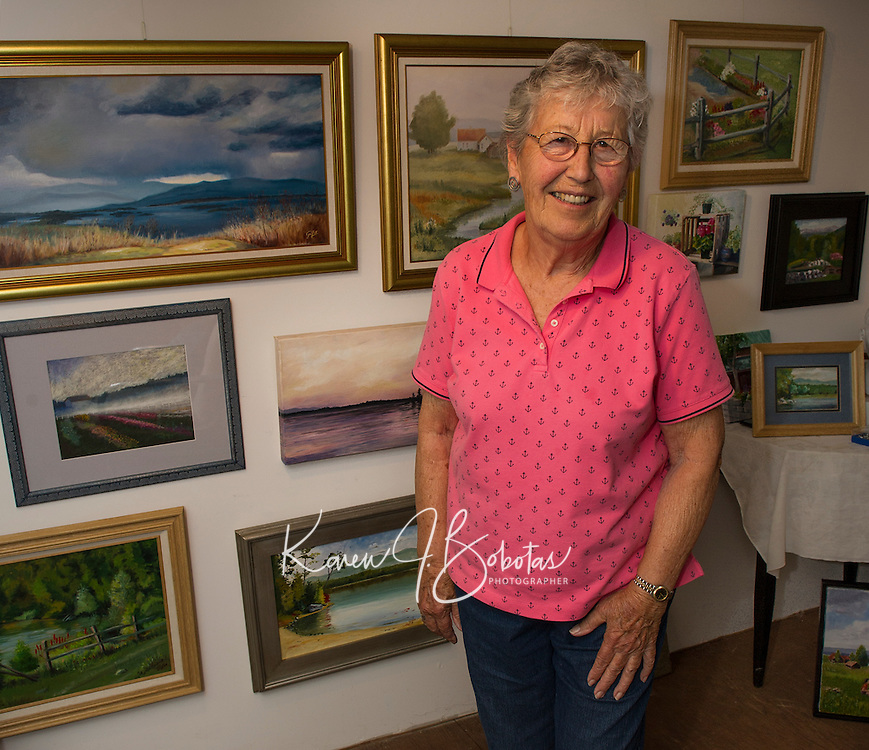 Gisela Langsten of the Lakes Region Art Association in her home studio with a backdrop of her oil and pastel paintings she has done depicting New England scenes as well as her various travel destinations.  (Karen Bobotas/for the Laconia Daily Sun)
