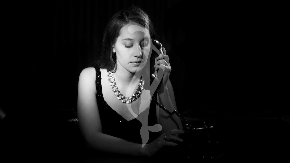 A model at a desk in a dark room.