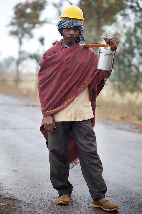 After a three hour shift crushing bauxite, an Adivasi (tribal) Baiga casual day-wage worker on his way home to the village of Kukra Pani village 8km away from the Bodhi Daldali Bauxite mine. Day-wage work at the mine will earn this man Rs.125 (bauxite fetches Rs.600-700 per ton). Located in the Maikal hill range, the 668 hectare Bodhi Daldali mine, run by Balco &amp; Vedanta (Vedanta is a UK headquartered company), has been operational since 2003. Many Baiga families living on the site of the mine were relocated to make way for the mine. Enticed by compensation and often empty promises of employment and health and education services, most relocated people have regretted moving from their ancestral lands. The mine directly employs just 70 people. 750 contractors, most of them casual day-wage workers, provide the labour without which the mine would not function. <br /> <br /> Photo: Tom Pietrasik<br /> Kawardha District, Chhattisgarh. India<br /> February 20th 2011