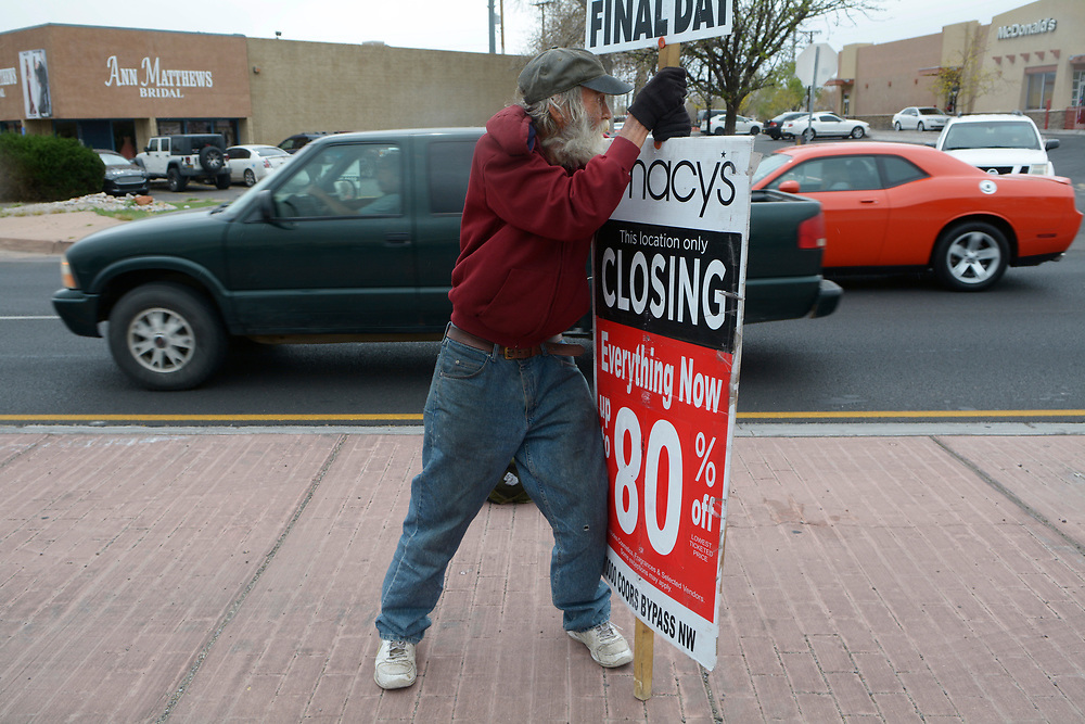 gbs032317h/ASEC -- Bill Petersen of Albuquerque braces his sign against the wind on Thursday, March 23, 2017. Petersen was at the intersection of Alameda and Coors with his Macy's closing signs from noon until 5 p.m.(Greg Sorber/Albuquerque Journal)