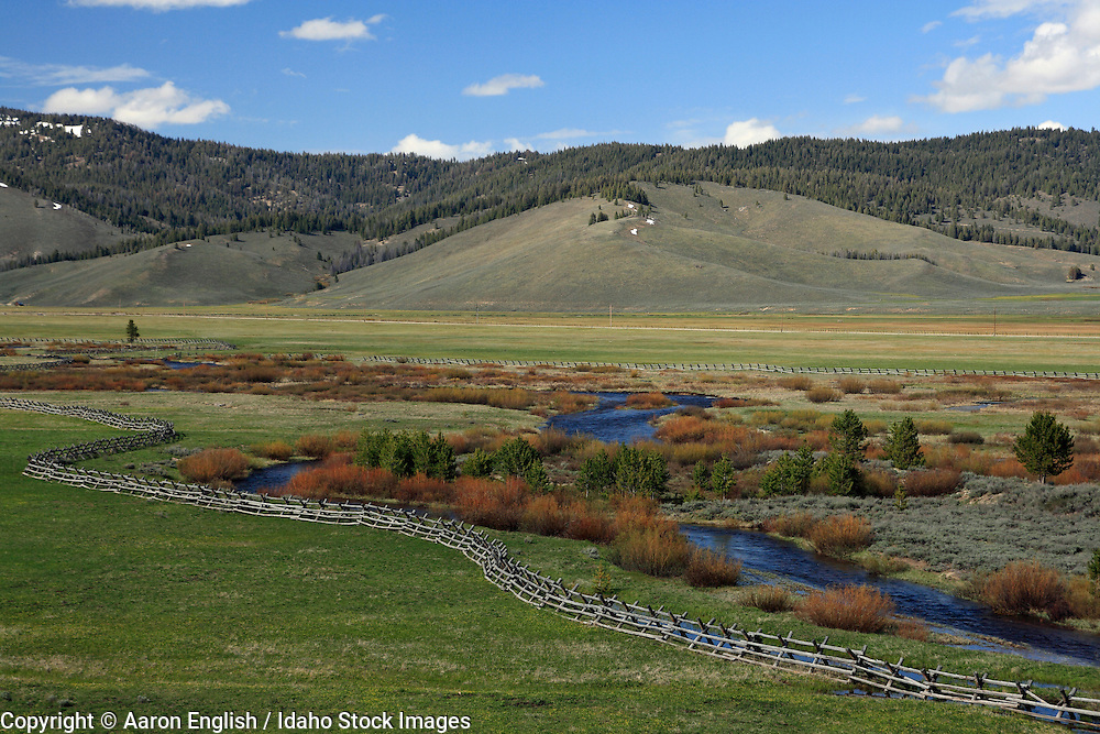 Valley Creek meanders, through meadows with pole fences with the foothills of the Salmon Mountains in the background, Stanley, Idaho