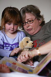 Young girl looking at a book with her Grandmother,