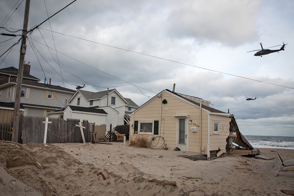 November 18, Ocean Beach, NJ, Helicopters fly over beach front homes destroyed by Superstorm Sandy's surge. Hurricane Sandy hit the Jersey Shore as a tropical storm causing billions of dollars of damage and cutting electricity to hundreds of thousands. Extreme weather is being blamed on climate change by many scientist.