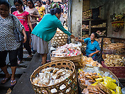 11 OCTOBER 2016 - UBUD, BALI, INDONESIA: A woman buys snacks from a vendor in the morning market in Ubud. The morning market in Ubud is for produce and meat and serves local people from about 4:30 AM until about 7:30 AM. As the morning progresses the local vendors pack up and leave and vendors selling tourist curios move in. By about 8:30 AM the market is mostly a tourist market selling curios to tourists. Ubud is Bali's art and cultural center.      PHOTO BY JACK KURTZ