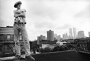 Man stood on roof top wearing denims and cap and 'Dilla named name belt, New York,  USA, 1980's