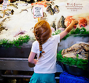 Young Red Head Reaching for the Red Fish at Pike Place Fish Market, Seattle