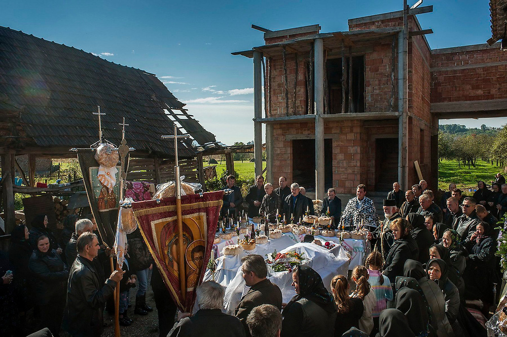 People gather for the funeral of an 84 year old man in the yard of his house. Next to his house his grandson who is working in Spain is building a new, much larger, house.