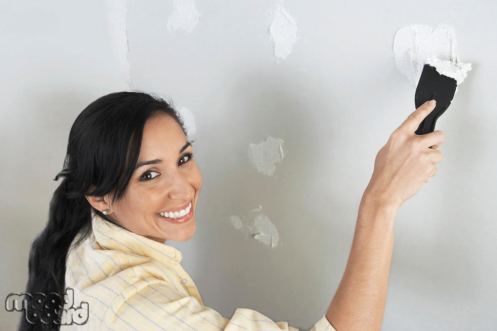 Woman Spackling Wall
