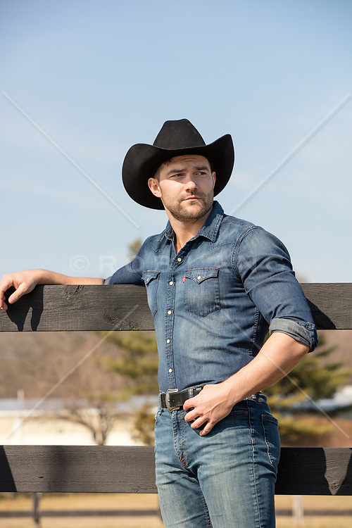 rugged cowboy leaning on a fence