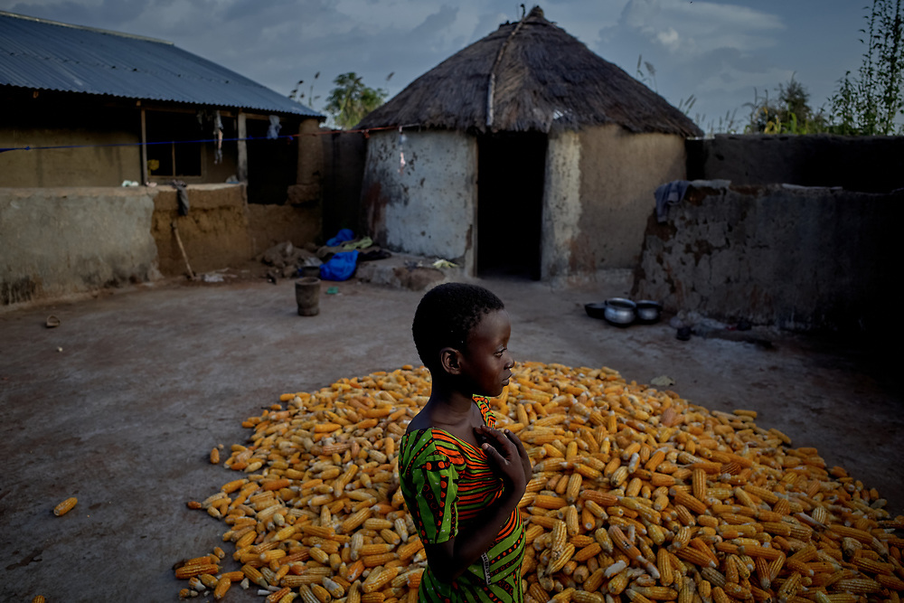 25/10/2019 / Kpatua / Ghana:<br /> Joyce walks past yellow maize being dried on their compound after harvesting.<br /> <br /> Oxfam built a solar powered pump in Kpatua to help over families become more resilient during dry seasons. Apart from community members coming to the pump twice a day, all year round, during the dry season, women use the water from the pump to farm vegetables for sale.