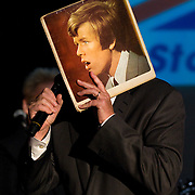 Peter Noone, of '60s rock group Herman's Hermits, performs as his 'younger self' while holding up an old album cover featuring a photo of himself brought to the show by a fan.
