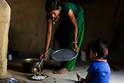 Pramila Tharu, 15, prepares lunch for her 2 year old toddler Prapti, in Bhaishahi village, Bardia, Western Nepal, on 29th June 2012. Pramila eloped and married at 12 and gave birth to Prapti at age 13. She delivered prematurely on the way to the hospital in an ox cart and her baby weighed only 1.5kg at birth. In Bardia, StC works with the district health office to build the capacity of female community health workers who are on the frontline of health service provision like ante-natal and post-natal care, especially in rural areas. Photo by Suzanne Lee for Save The Children UK