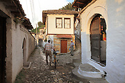 Man wheeling his bicycle in the narrow streets amongst the houses in the Gorica Quarter in Berat, South-Central Albania, capital of the District of Berat and the County of Berat. Picture by Manuel Cohen