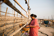 A local women hangs fish on long racks to dry them in the sun. This area is famous for its dried fish.