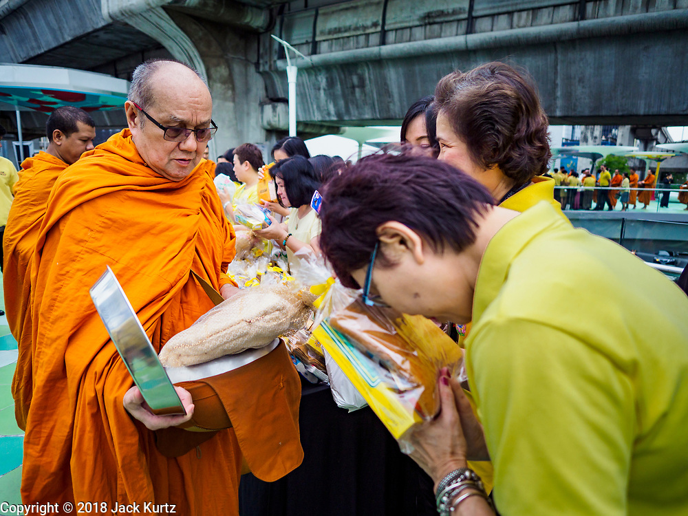 26 JULY 2018 - BANGKOK, THAILAND:  A woman prays before making a donation to a monk during a merit making ceremony in the Pathumwan area of Bangkok to honor Thai King His Majesty King Maha Vajiralongkorn Bodindradebayavarangkun, also known as Rama X, for his 66th birthday. The King's birthday is 28 July, and events are scheduled throughout Thailand to honor His Majesty. The Pathumwan merit making was organized by businesses in the area.       PHOTO BY JACK KURTZ