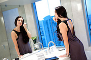 Pretty Brunette Applying Makeup In Bathroom