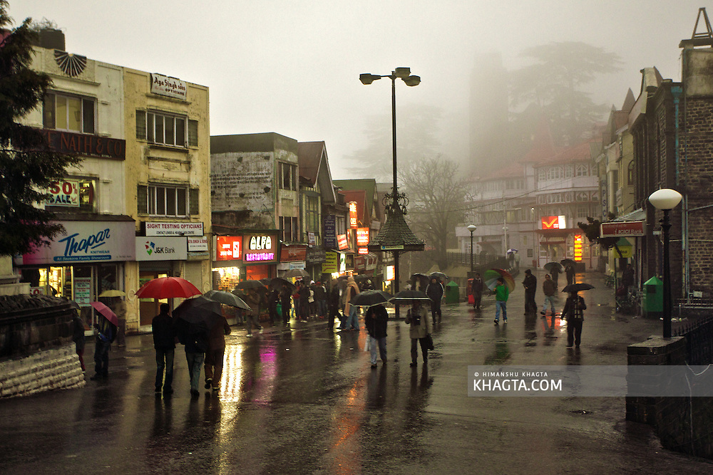 People strolling near the Scandal Point of The Mall Road of Shimla, Himachal Pradesh in a foggy and rainy monsoon evening