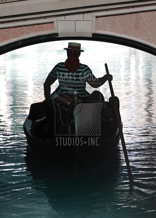 Gondolier navigating a gondola under a bridge