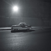 Grainy black/white shot of Nash Metropolitan parked under a freeway overpass bridge under a street light.