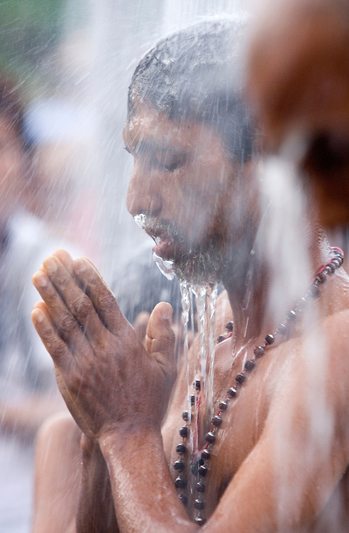 """Hindu devotee takes a shower before their pilgrimage to the sacred Batu Caves temple during the Thaipusam festival in Kuala Lumpur, Malaysia. Hindu devotees celebrate Thaipusam festival in honour of the Lord Murugan (also known as Lord Subramaniam). Thousands of Hindu devotees carried the milk pots and """"kavadi"""" (a gaily decorated wooden or metal frame) walk barefoot up the temple's 272 steps to undergo penance in fulfilling vows made to Lord Murugan for answering their prayers."""