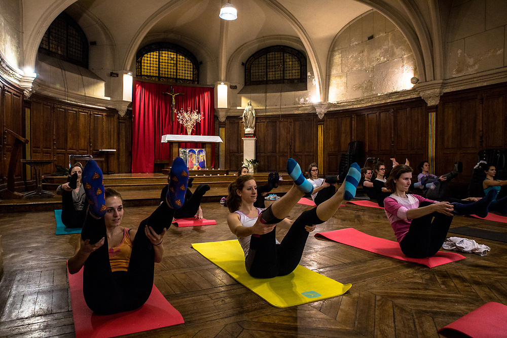 Young women exercise at a session organized by the Body & Mind association, which organizes spiritual and exercise sessions for young women in the crypt of Paris' Trinity church.  Paris, France.  February 20, 2017.                      © Daniel Barreto Mezzano
