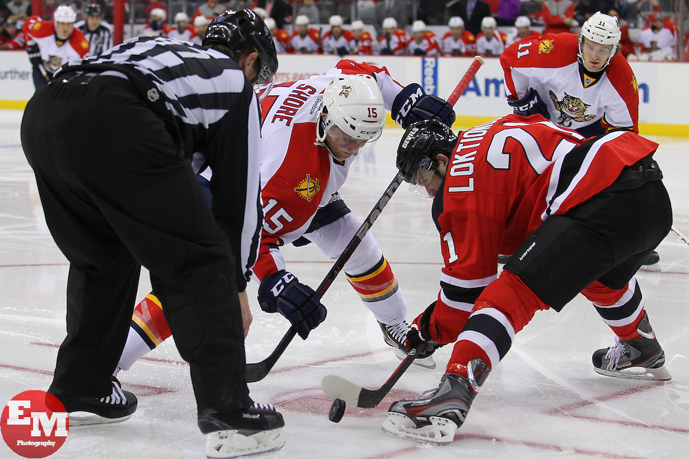 Mar 23, 2013; Newark, NJ, USA; Florida Panthers center Drew Shore (15) and New Jersey Devils center Andrei Loktionov (21) face off during the second period at the Prudential Center.