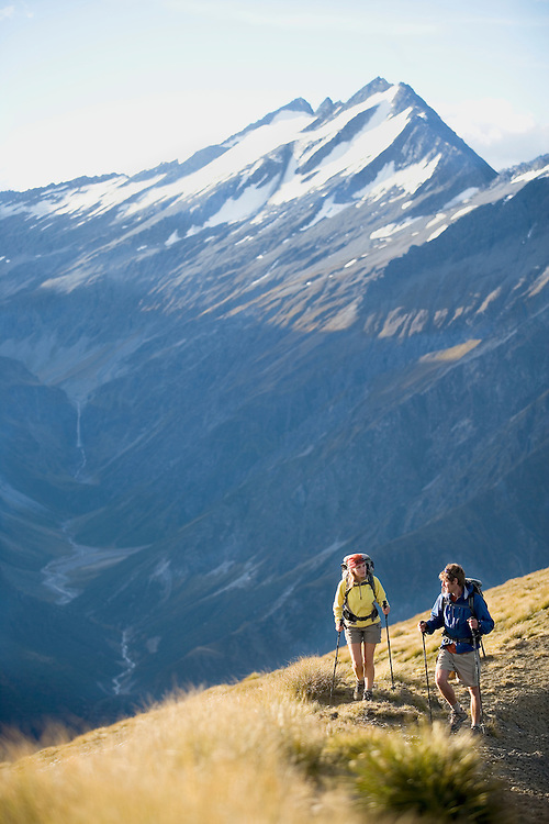 Two hikers in New Zealand hiking on open ridge line with snow covered mountains in the background and fall grasses in the foreground