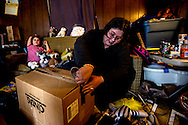 Genesis Shearn tapes up a box during the last minute packing rush on moving day. Genesis and her fiance, Jason Fogle, found a new home in Heath just as the deadline to vacate the Raccoon Creek Trailer Park drew near.
