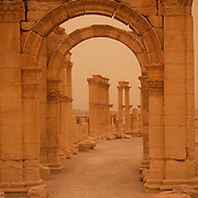 Ruins of monumental arch and colonnade, seen through settling dust just after a sandstorm, Palmyra