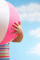 Girl (7-9 years) holding beach ball in front of face close up