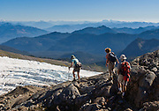 Hikers near Easton Glacier, Mt Baker, hiking to the end of the Railroad Grade, a lateral moraine of the Easton Glacier on the south side of Mount Baker. Mount Baker National Recreation Area, Washington, USA.