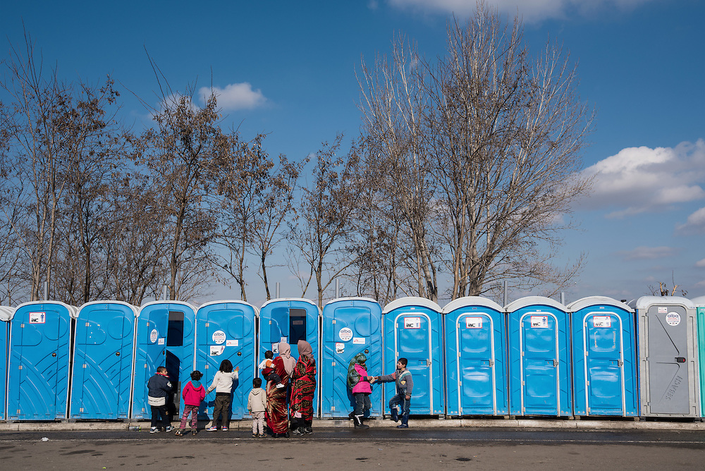 Refugee women and their children at the portable toilets at the petrol station near Idomeni. In the last few months the fields near this petrol station have become a transit camp for thousands of refugees and migrants waiting to cross to Greek Macedonian border.
